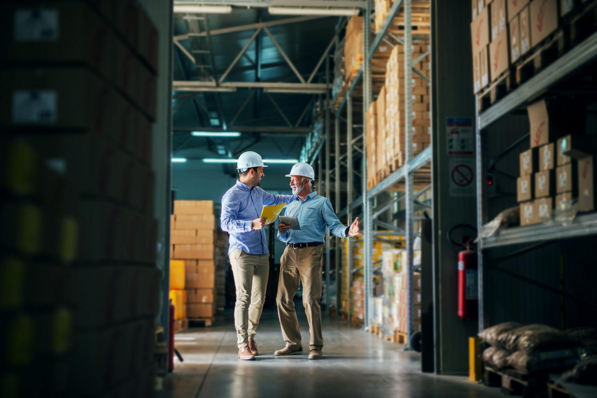 Two men laughing and looking at each other in a warehouse